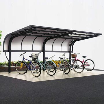 サイクルポート シンプルなサイクルポート。アール形状の垂れ下がり屋根が雨の吹き込みを防止。梁・柱を1本のスチール材&アルミカバーで構成したシンプルなデザインのサイクルポートです。雨・風の吹き込みを防ぐパネルや、キーチェーンを付けることができる車止めバーなどもご用意しています。