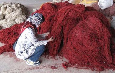 染め上げられたギャッベ(ギャベ)の糸の出来を確認する店長 イラン・シラーズの染色工房にて