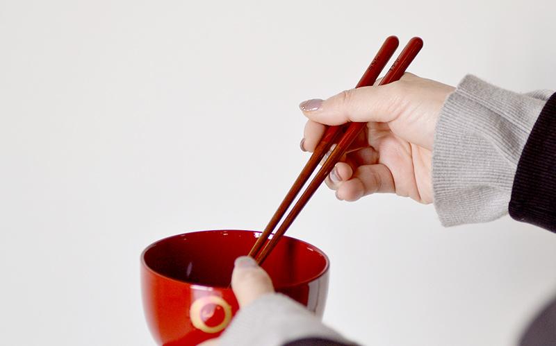 成人女性がおわんとお箸を持っている画像